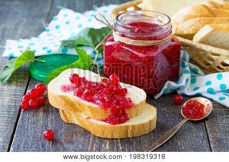 Homemade Jam. A Glass Jar With Red Currant Jam And White Bread On A Kitchen Wooden Table. Preserved