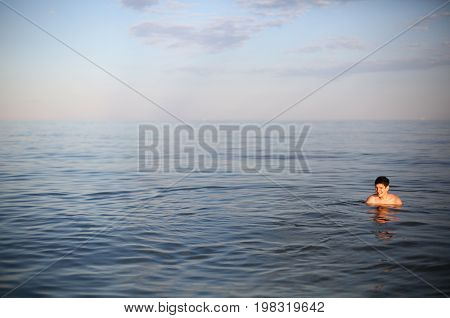 Young boy with brown hair while bathing in the sea at sunset