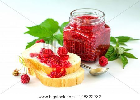 Homemade Jam And White Bread. Glass Jar With Raspberry Jam On A White Background. Preserved Berry.