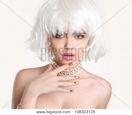 Beauty Blonde. Blond bob hairstyle. Fashion girl model with makeup, short hair, manicured nails, golden jewelry set isolated on white background.