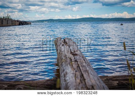 View from the logs lying on the sandy shore of the lake on the opposite shore, hills, sky and thick clouds.