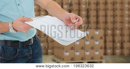 Delivery man with clipboard asking for signature against brown cardboard boxes over white background