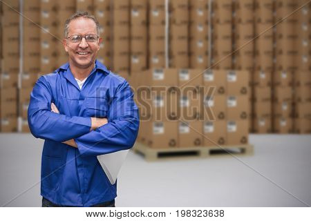 Smiling warehouse manager standing with arms crossed against grey background