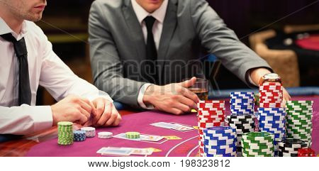 Stack of colorful casino tokens with red dice against men placing bets at poker game