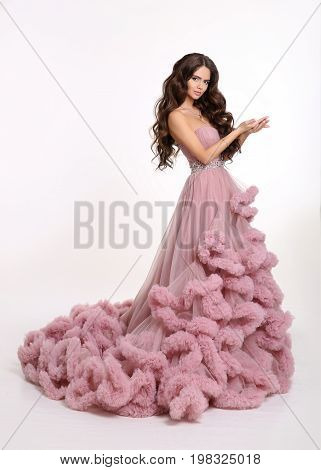 Beautiful girl Lady in luxury lush pink dress. Fashion brunette woman in gorgeous long gown posing isolated on white studio background.