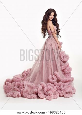 Beautiful Lady in luxury lush pink dress. Fashion brunette woman in gorgeous long gown posing isolated on white studio background.