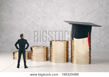 Back view of businessman looking at golden coin piles with mortarboard on concrete background. College savings concept. 3D Rendering