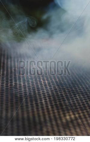 The smoke of the fire seeps through the perforated grate.