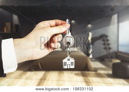 Close up of businessman hand holding key with house keychain on blurry bedroom interior background. Real estate concept. 3D Rendering