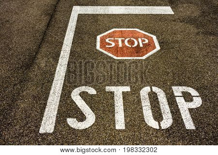 stop sign on city asphalt floor with red symbol and withe line