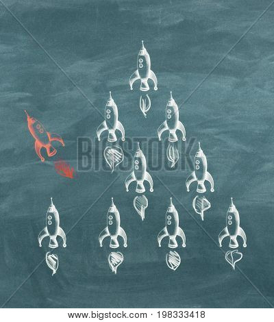Chalkboard wall with different drawn rockets. Leadership concept