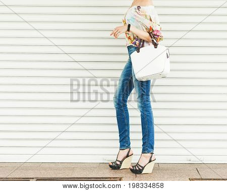Close up of stylish female leather bag outdoors. Fashionable and high style expensive female bag. Sales bag fashion concept. Part of body. On red wood background. High Wedge Sandals. Part of body.