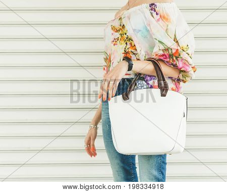 Close up of stylish female leather bag outdoors. Fashionable and high style expensive female bag. Sales bag fashion concept. Part of body. Street style.