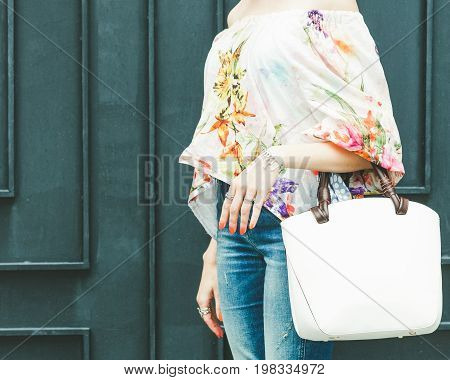 Close up of stylish female leather bag outdoors. Fashionable and high style expensive female bag. Jeans and fashionable colored blouse. Sales bag fashion concept. Part of body. Street style. Outdoor.