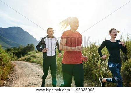 Three Friends Cross Country Running Together On A Trail