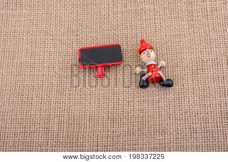 Pinocchio Sitting Beside Holding A Notice Board