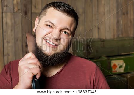thick man shaves his beard with a sharp knife against the background of a wooden wall and army boxes with weapons