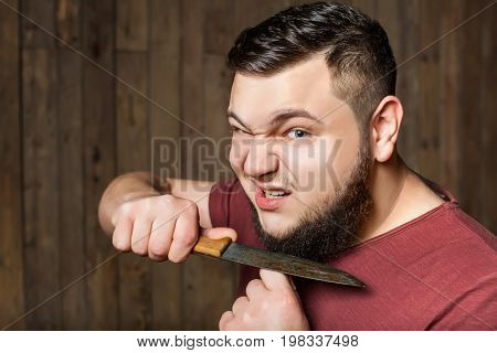 brutal thick man shaves his beard with a sharp knife against the background of a wooden wall