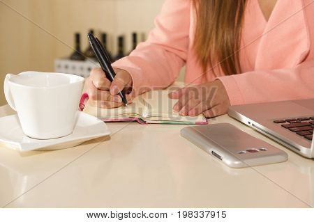 Close up of businesswoman hand working and holding with one hand a pen and writting on an agenda the activity schedule. Business concept.