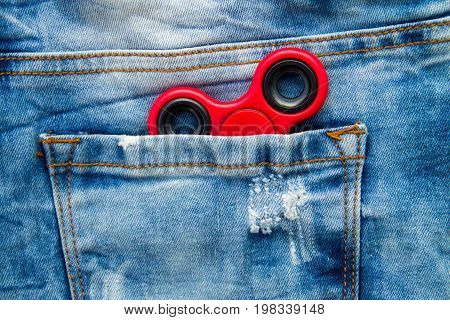 Red Fidget Spinner Stress Relieving Toy In Pocket Of Blue Jeans