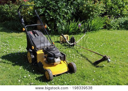 Gardening equipment mower and brush cutter in a garden during spring