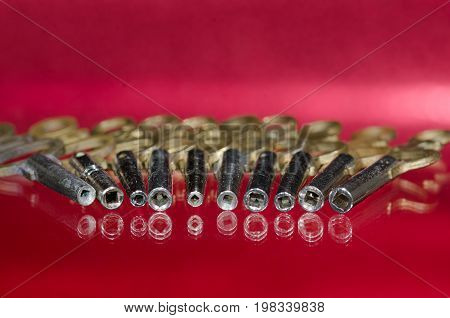 View Into the Barrel of a Row of Antique Pocket Watch Keys on a Red Surface