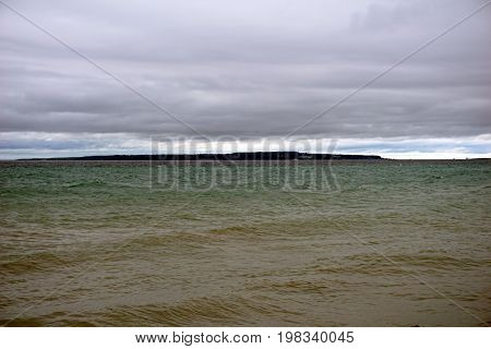 A view of the Straits of Mackinac, and Mackinac Island, as seen from Alexander Henry Park in Mackinaw City, Michigan, during a cloudy day in June.