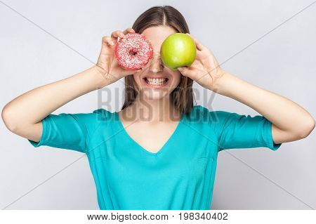 Beautiful young woman with freckles in green dress holding before her eyes green apple and pink donut and shows her teeth. studio shot on light gray background.