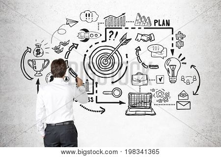 Rear view of a young business coach drawing a black business goal sketch on a concrete wall. Concept of analysis