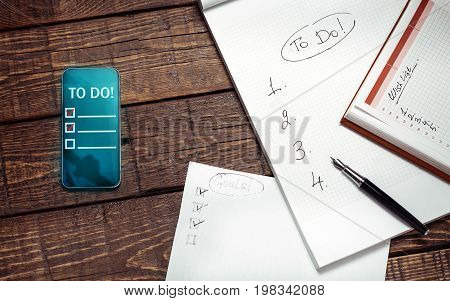 Paper And Electronic To Do Lists On Wooden Surface Top View. Memo Planning Technology Concept