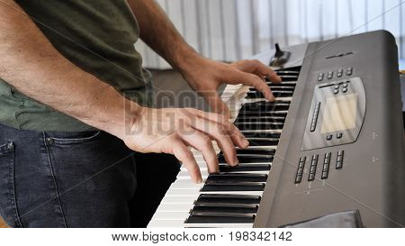 Side view of male musician playing electric piano or electronic keyboard or synthesizer at home.