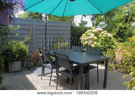 Flowered terrace with gray garden furniture and green sunshade