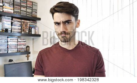 Confused or doubtful young man scratching his chin and looking at camera. Indoor at home