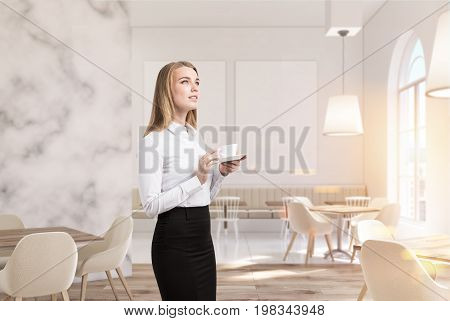 Marble cafe interior with white walls large windows beige sofas and chairs and square wooden tables. An inspired blonde businesswoman. 3d rendering mock up toned image
