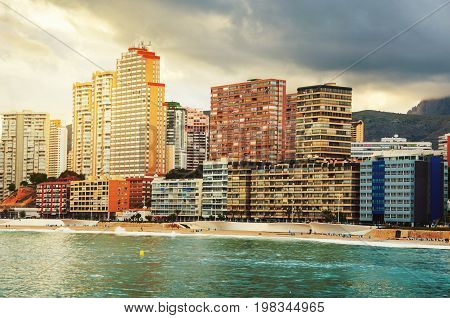 Benidorm, Spain. Summer resort Benidorm, Spain with beach and famous skyscrapers in the evening. Colorful cloudy sky