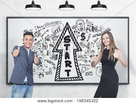 Asian businessman and his blonde colleague wearing an elegant black dress. They are showing thumb up signs and smiling. Whiteboard background startup arrow sketch.