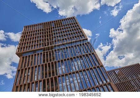 Veiw on new loft style modern building made of brown bricks with big wide windows EGODOM. Rectangular building architecture. Russian modern loft architecture. Luxury real estate
