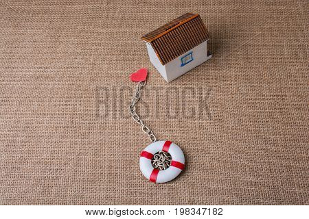 Model house and a life preserver with a heart on a chain