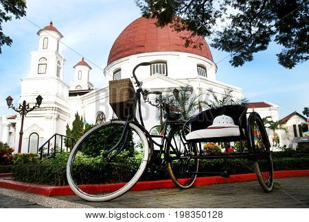 Classic bycicle at the park in the front of ancient church called