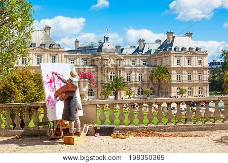 PARIS, FRANCE - JUNE 9, 2012: An unidentified female artist painting in the Luxembourg Gardens in Paris, France, with the Luxembourg Palace in the background.