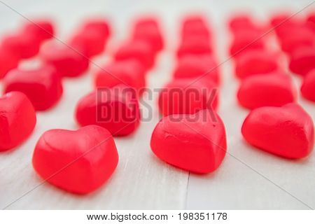 Red Gummy Heart in Focus at the end of diagonal rows