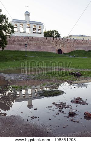 bell tower of the Novgorod Kremlin and the medieval fortress wall of the Kremlin from terracotta bricks reflected in the water puddles green grass