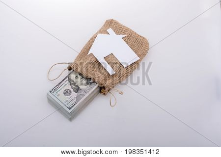 Paper house placed beside a bundle of US dollar banknote