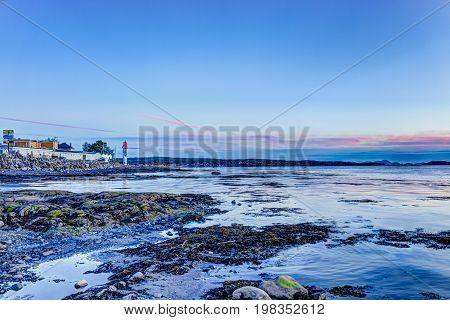 Rimouski Canada - June 4 2017: Purple sunset in Gaspesie region of Quebec by Saint Lawrence river with rock boulders in shallow water and seaweed with Motel sign