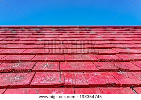 Macro Closeup Of Red Painted Wooden Shingle Roof Panels With Blue Sky
