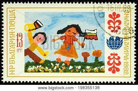 Moscow Russia - August 03 2017: A stamp printed in Bulgaria shows children's drawing of Holiday people with a flag series