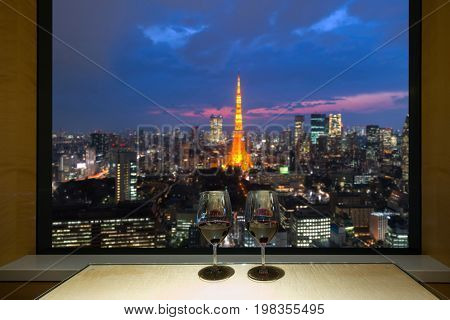 Closeup of a glasses of red wine at windowsill against night Tokyo city view of urban city sky line blurring lights. Japan.
