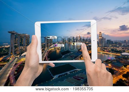 Hand holding smart phone use AR application to check relevant information about the spaces around customer. Singapore City in background. Augmented reality marketing concept.