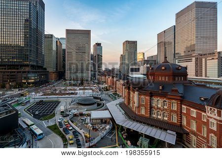 Tokyo railway station and Tokyo highrise building at eveing time in Tokyo Japan. poster