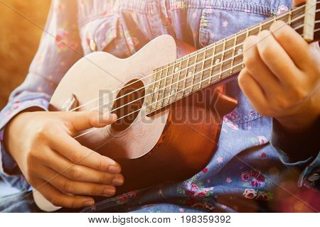 Close-up of little hipster girl playing ukulele guitar vintage film tone effect